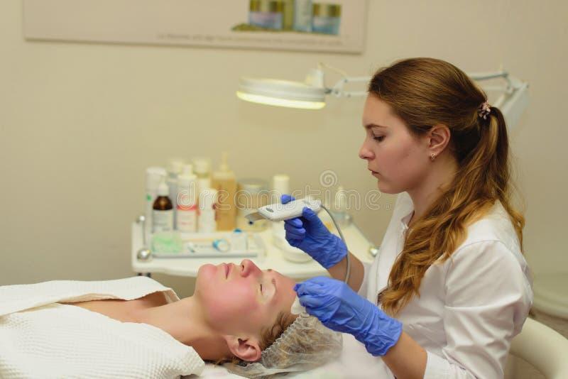 Ultrasone scraber Echt schot van procedure van het ultrasone schoonmaken van gezicht Cosmetologicalkliniek Gezondheidszorg, klini royalty-vrije stock afbeeldingen
