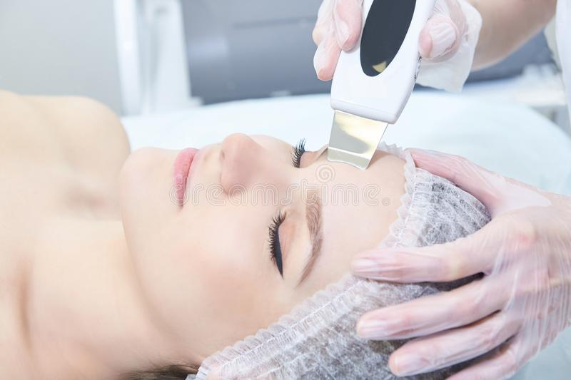 Ultrasonic cleaning of the face. Modern equipment. Cosmetic clinic procedure. Young girl model stock image
