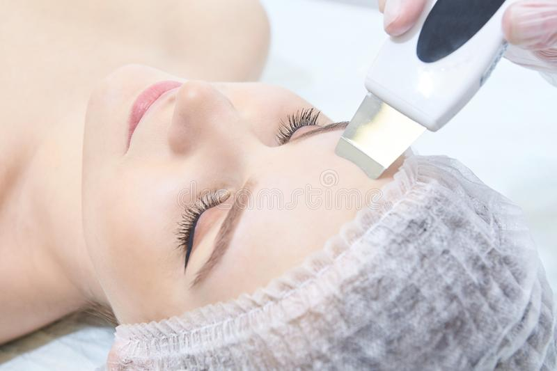 Ultrasonic cleaning of the face. Modern equipment. Cosmetic procedure. Young girl stock images