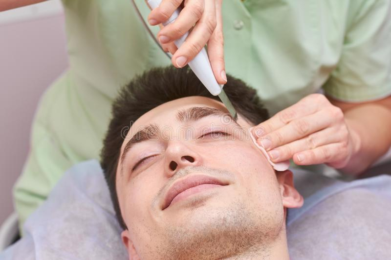 Ultrasonic face cleaning, young man. stock photography