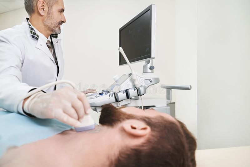 Ultrasound diagnostics of neck lymph nodes. Sonography, ultrasound diagnostics of lymph nodes on neck. Bearded men lying in medical cabinet. Doctor wearing in stock photos