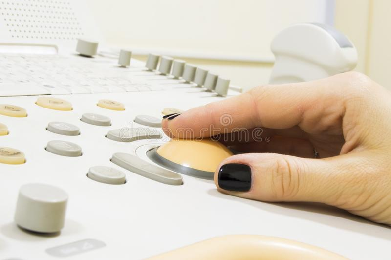 Ultrasound examination. Hand of doctor or technician is on trackball of ultrasound machine with probe sensor, transducer on bac. Kground, performing ultrasound royalty free stock image
