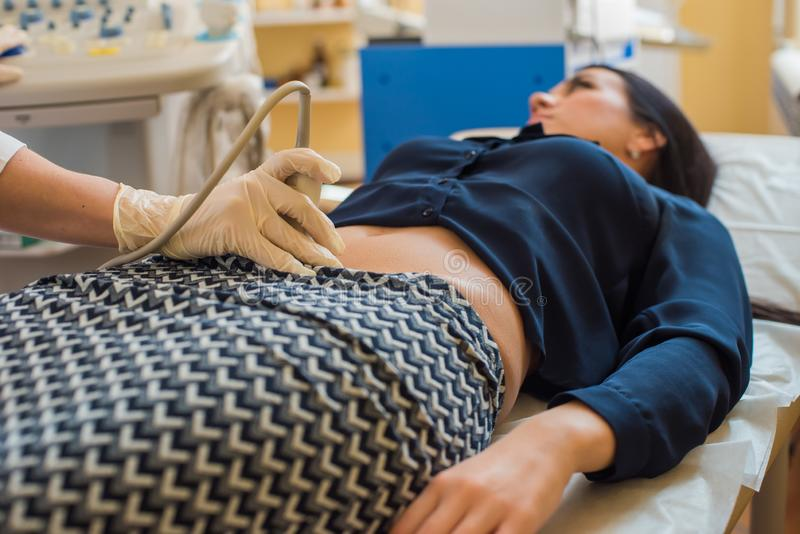 Ultrasound test. Pregnancy. Gynecologist checking fetal life with scanner. Exam. stock photos