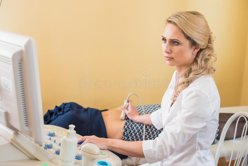 Ultrasound test. Pregnancy. Gynecologist checking fetal life with scanner. Exam. royalty free stock photography