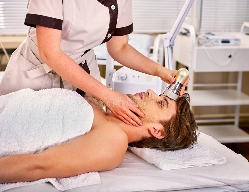 Ultrasound therapy for male skin tightening in beauty spa salon stock photo