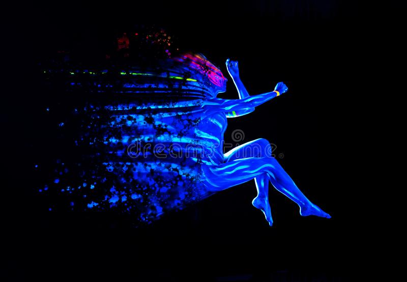 Ultraviolet black light glowing bodyart on young woman`s body. Dispersing girl on black background. Art creative concept royalty free stock images