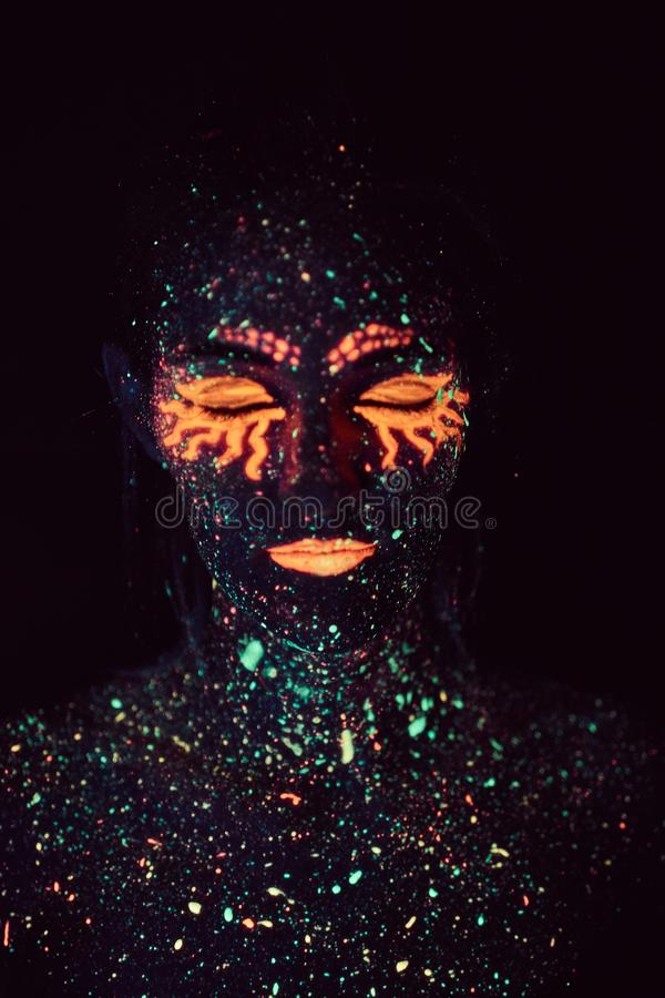 Portrait of a girl painted in fluorescent powder. Halloween concept. stock photos