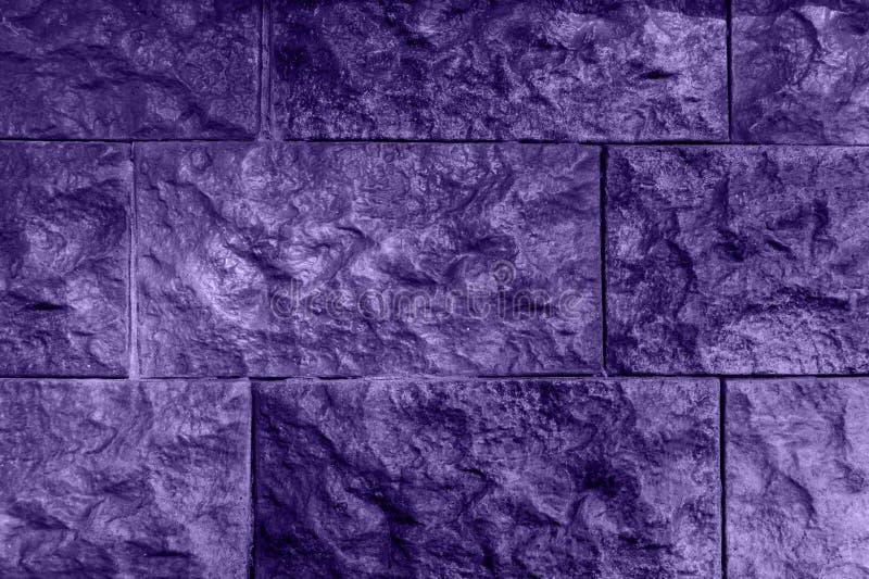 Ultraviolett bakgrund, vägg från lättnadstegelsten royaltyfri fotografi