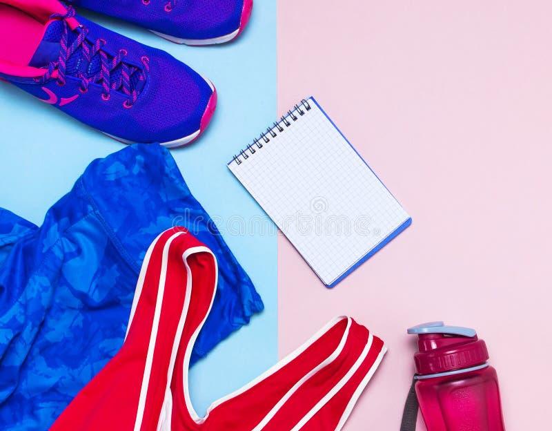Ultravioletta kvinnliga gymnastikskor, blå sportslig damasker för rosa överkant och vattenflaska på pastellfärgad rosa plan lekma arkivbild
