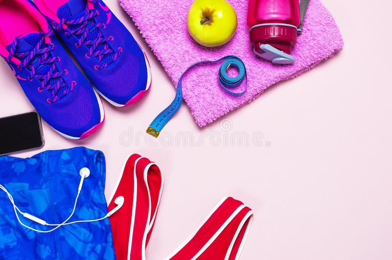 Ultraviolette weibliche Turnschuhe, rosa oberste blaue Sport- Gamaschen und Wasserflasche auf rosa gelegter Pastelldraufsicht des lizenzfreie stockfotos