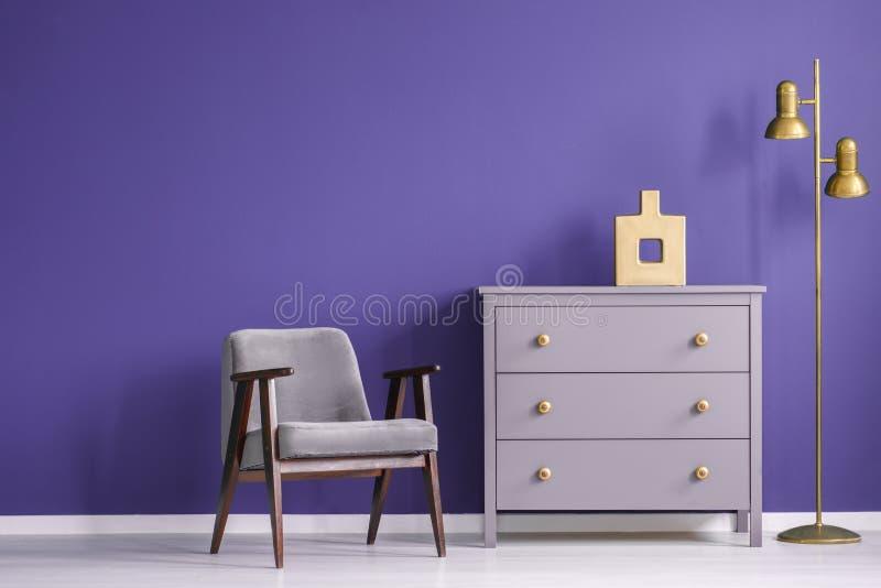 Ultravioletter Wohnzimmerinnenraum mit Retro- Lehnsessel und Kasten stockfotos
