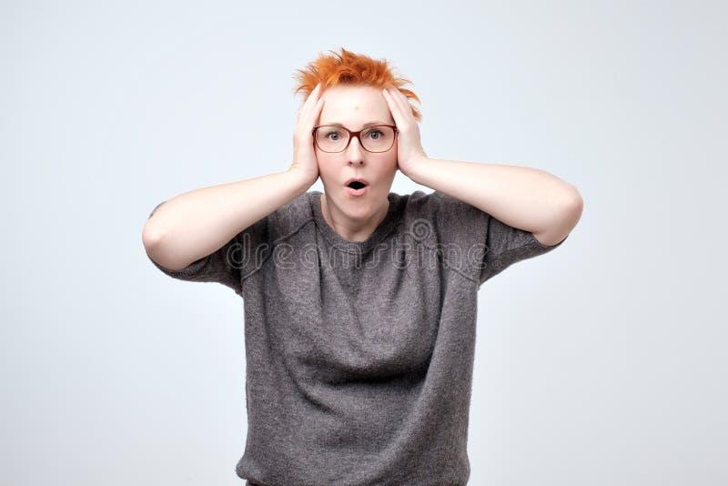 ululación Mujer caucásica hermosa con el pelo rojo aislado en backgroud gris del estudio fotografía de archivo