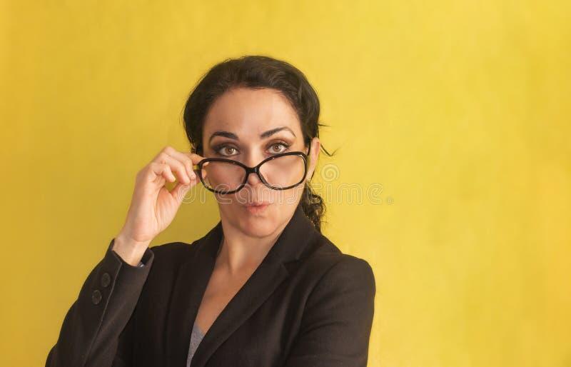 ululación Mujer de negocios joven hermosa, con la coleta, los vidrios y la chaqueta negra, aislados en un fondo Sorprendido, pasm fotos de archivo
