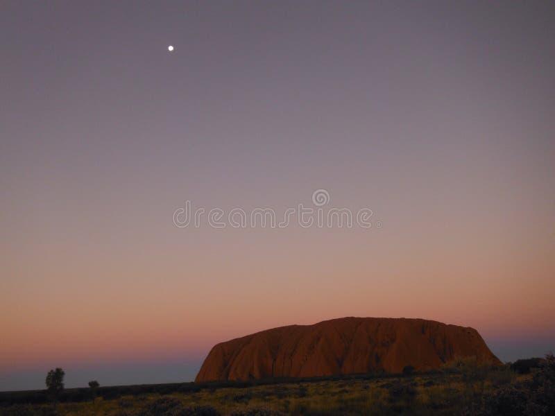 Uluru en la noche con la estrella en esquina superior imágenes de archivo libres de regalías