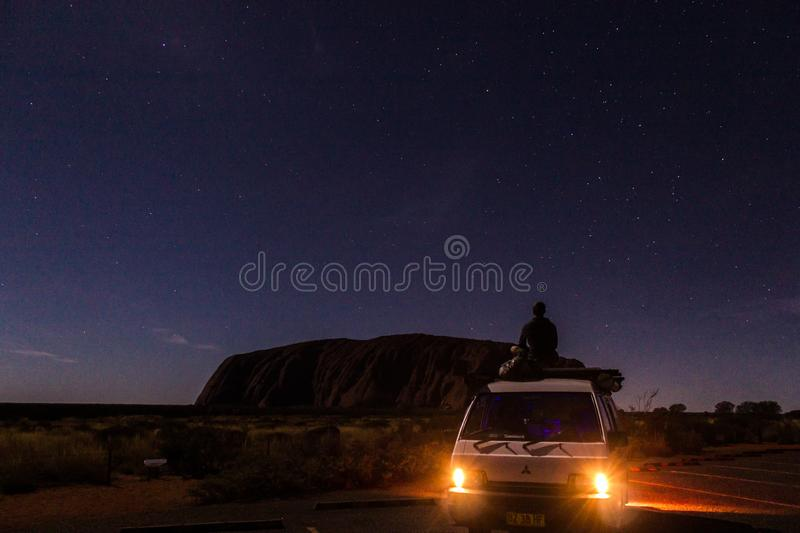 Uluru at night with car with a young man on the car, ayers Rock, the Red Center of Australia, Australia royalty free stock images
