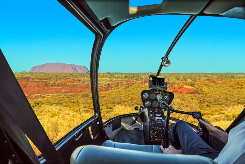 Uluru scenic flight. Scenic flight over Uluru. Helicopter cockpit aerial view of monolith rock formation in Uluru-Kata Tjuta National Park, Northern Territory stock photos