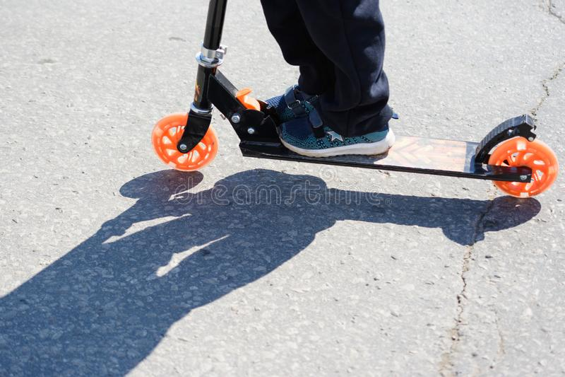 Ulyanovsk, Russia - April 20, 2019: children dangerously ride scooters on the roadway. Riding scooters. Road safety. Not safe pede stock photos
