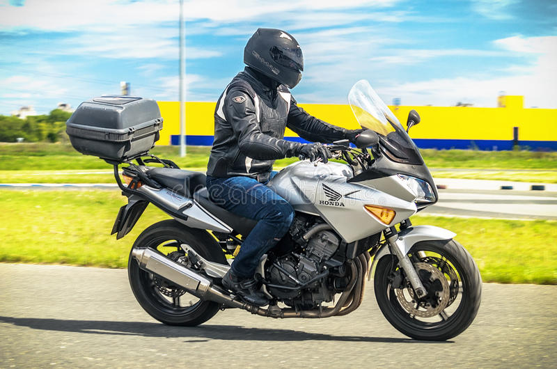 Ulyanovsk, Russia - June 10, 2017. A motorcycle racer in a black helmet with a backpack trains on a motorcycle with road. Ulyanovsk, Russia - June 10, 2017. A stock images