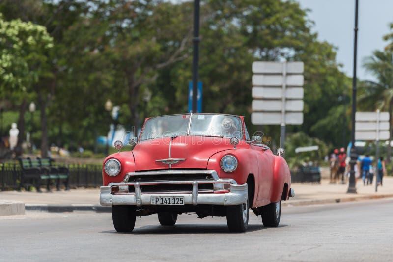 Um único cabriolet americano vermelho do carro do vintage conduz na estrada em Havana City fotos de stock