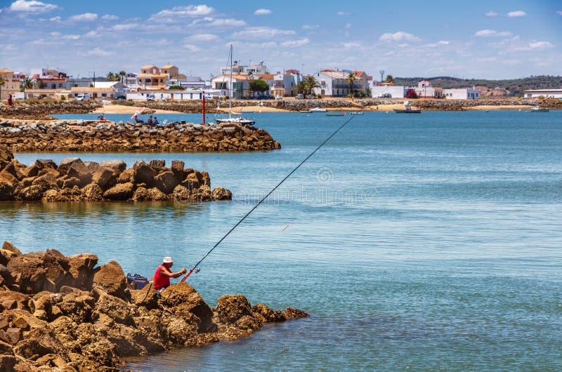 Um único pescador em uma camisa vermelha senta-se nas rochas que olham transversalmente a uma aldeia piscatória catita fotografia de stock royalty free