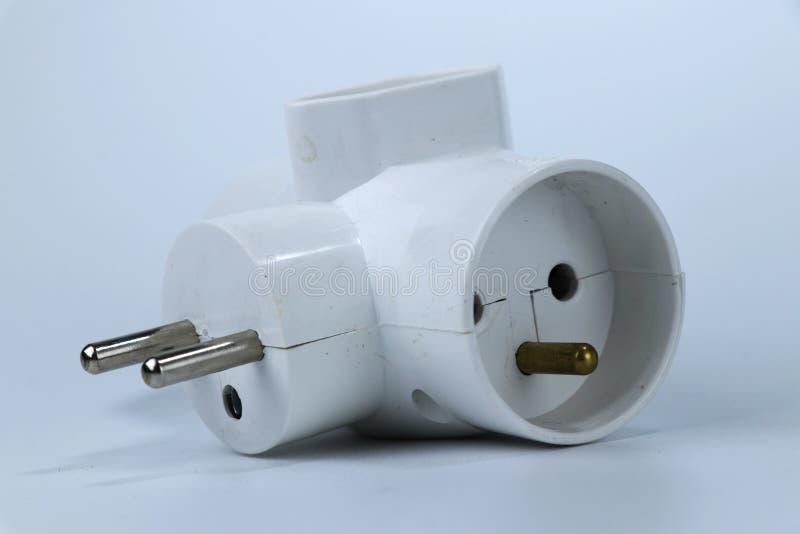 Um adaptador de três maneiras para conecta outros três cabels a um soquete europeu fotos de stock