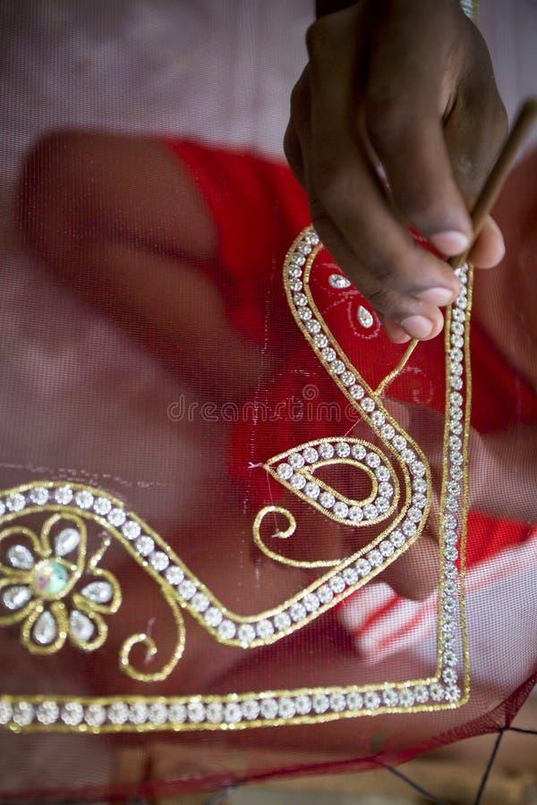 Um adolescente adiciona o detalhe a um saree tradicional de Jamdani em Mirpur Benarashi Palli, Dhaka, Bangladesh imagem de stock