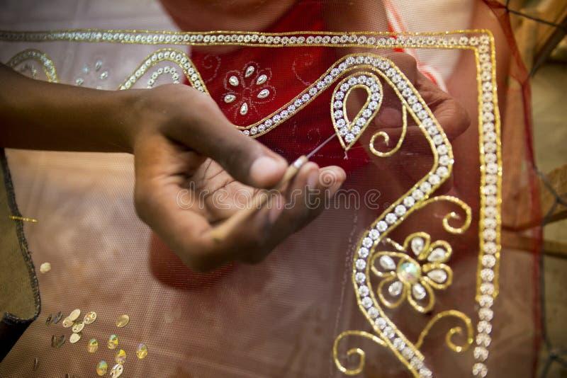 Um adolescente adiciona o detalhe a um saree tradicional de Jamdani em Mirpur Benarashi Palli, Dhaka, Bangladesh fotografia de stock royalty free