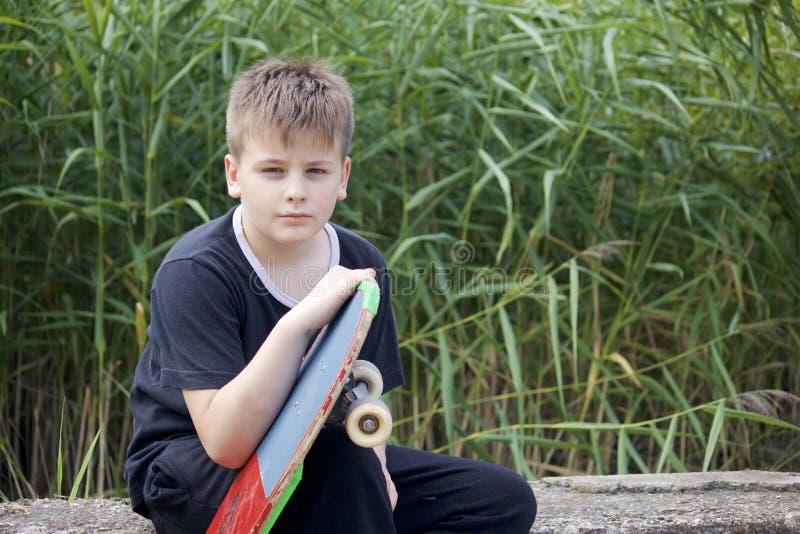 Um adolescente com um skate Guarda um patim nas mãos fotografia de stock royalty free
