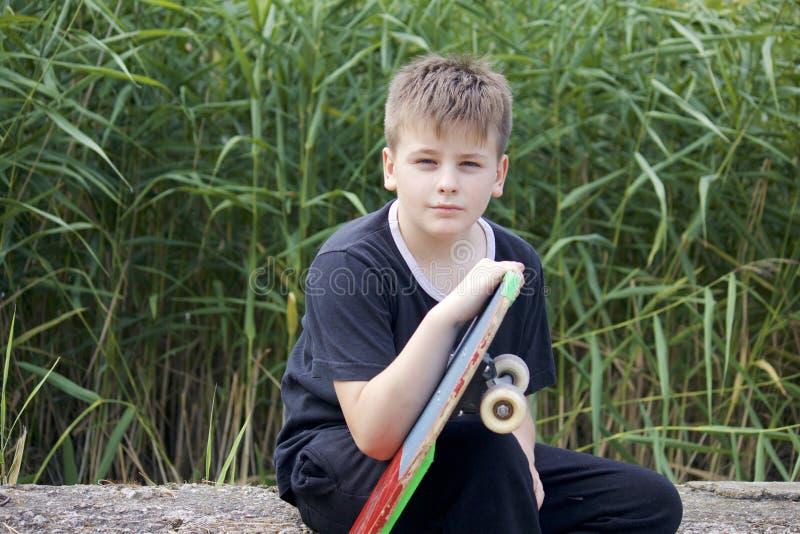 Um adolescente com um skate Guarda um patim nas mãos fotografia de stock
