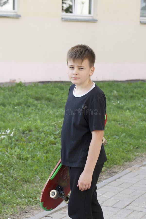 Um adolescente com um skate Guarda um patim nas mãos foto de stock royalty free