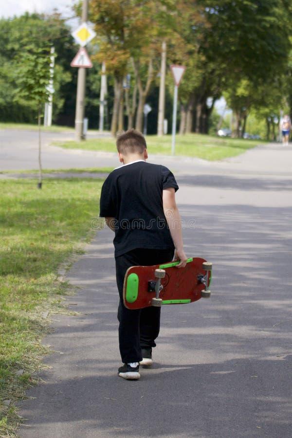 Um adolescente com um skate Guarda um patim nas mãos imagem de stock