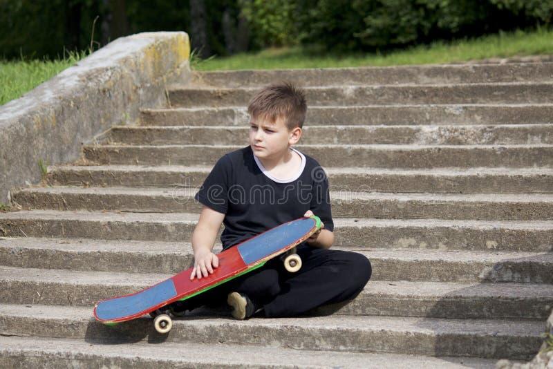 Um adolescente com um skate Senta-se com um skate contra o contexto de uma escadaria de pedra foto de stock