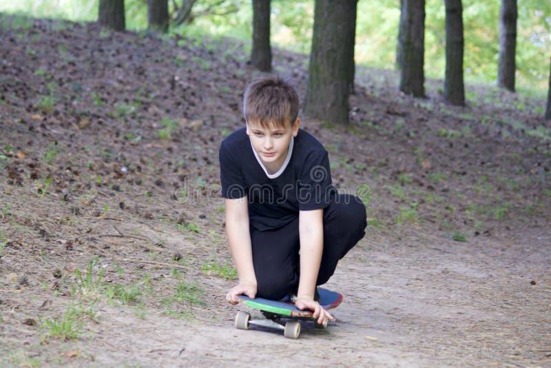 Um adolescente com um skate Senta-se em um skate imagem de stock