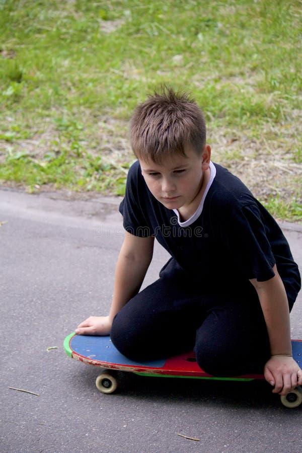 Um adolescente com um skate Senta-se em um skate foto de stock royalty free