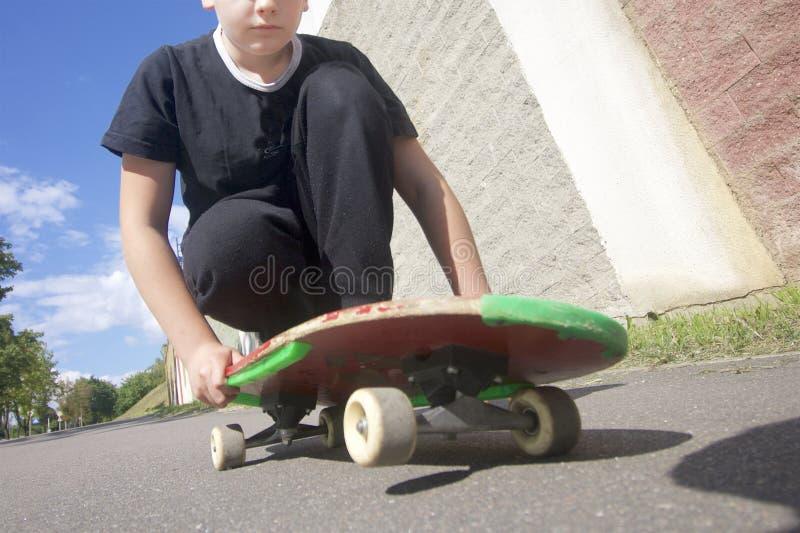 Um adolescente com um skate Senta-se em um skate imagens de stock