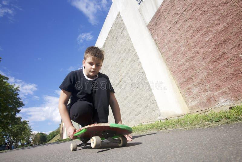 Um adolescente com um skate Senta-se em um skate fotos de stock royalty free