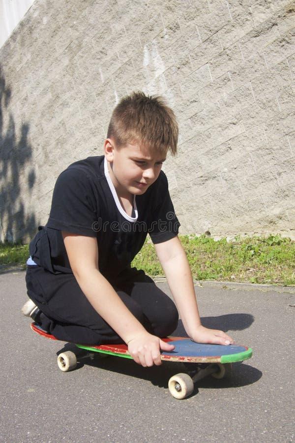 Um adolescente com um skate Senta-se em um skate fotos de stock