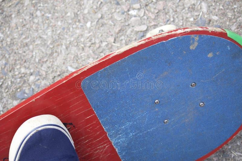 Um adolescente com um skate Senta-se em um skate Vista de acima imagens de stock