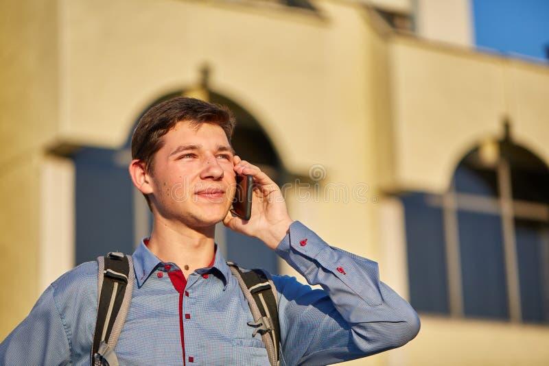 Um adolescente considerável taling em seu telefone ao andar em torno da cidade no fundo da construção foto de stock royalty free