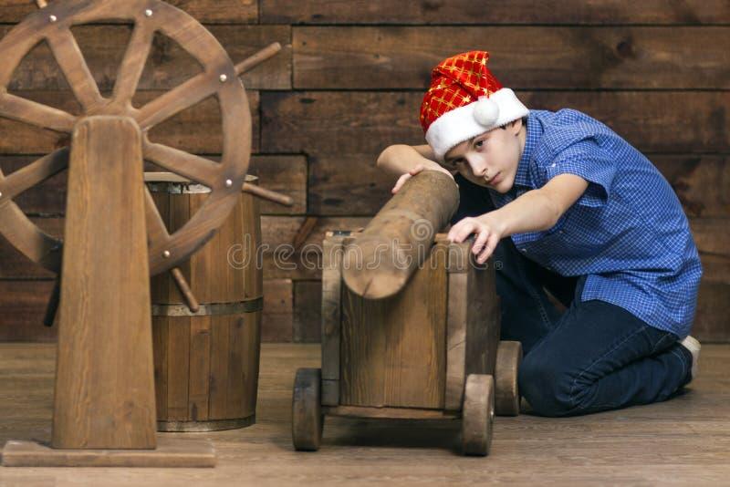 Um adolescente em um chapéu de Santa Claus com uma expressão séria em sua cara sugere um modelo da arma perto do tambor e do wh d fotografia de stock