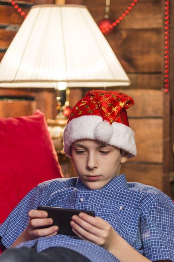 Um adolescente em um chapéu de Santa Claus guarda um telefone celular em suas mãos e olha pensativamente nele que senta-se pela l fotografia de stock royalty free