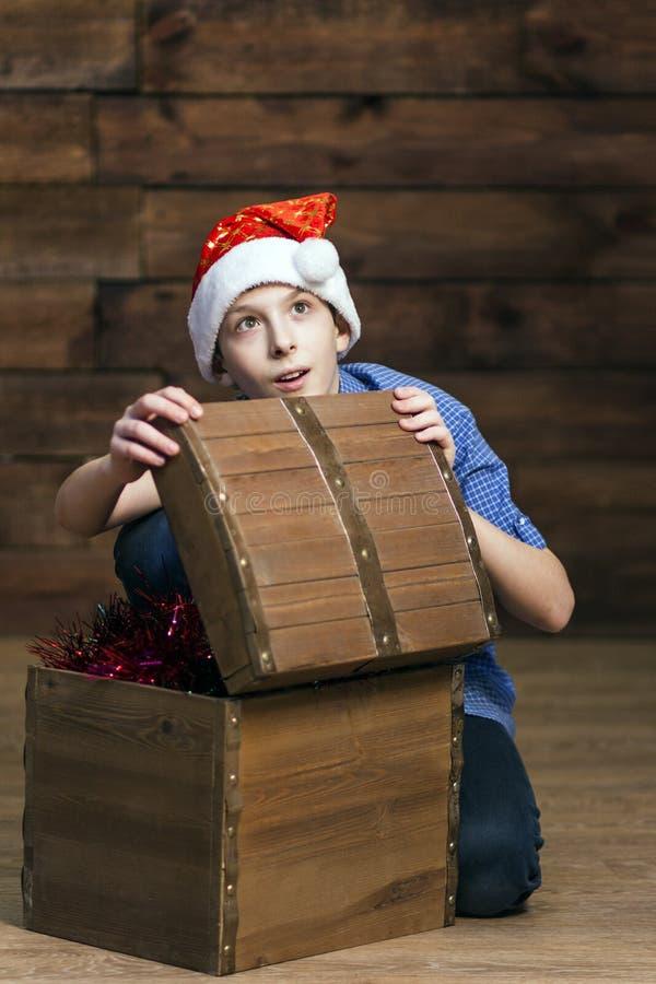 Um adolescente em um chapéu de Santa Claus, nas calças de brim, em uma camisa azul, abre a caixa com decorações do Natal e olha a foto de stock royalty free