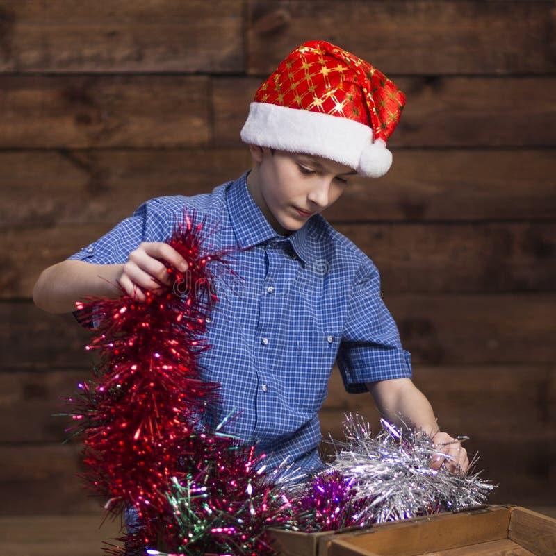 Um adolescente em um chapéu de Santa Claus olha em uma caixa de madeira aberta e retira decorações do Natal dela fotografia de stock royalty free