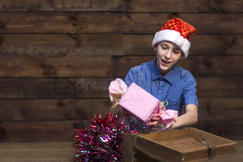 Um adolescente em um chapéu de Santa Claus, em uma camisa quadriculado azul retira felizmente um presente de uma caixa de madeira fotos de stock