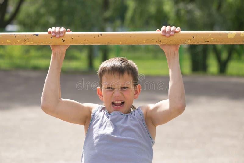 Um adolescente em um t-shirt é contratado na ginástica em uma barra horizontal imagens de stock
