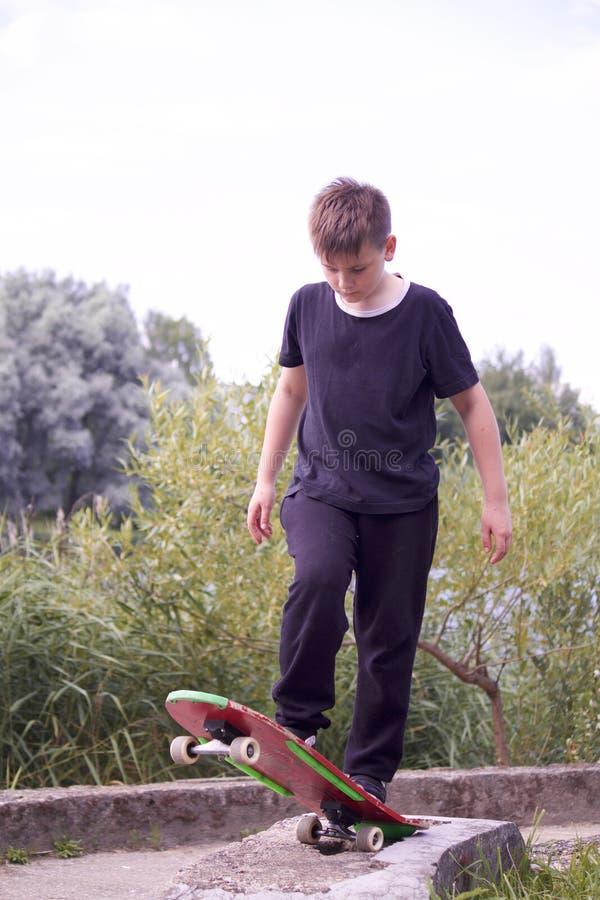 Um adolescente está estando em um skate imagens de stock
