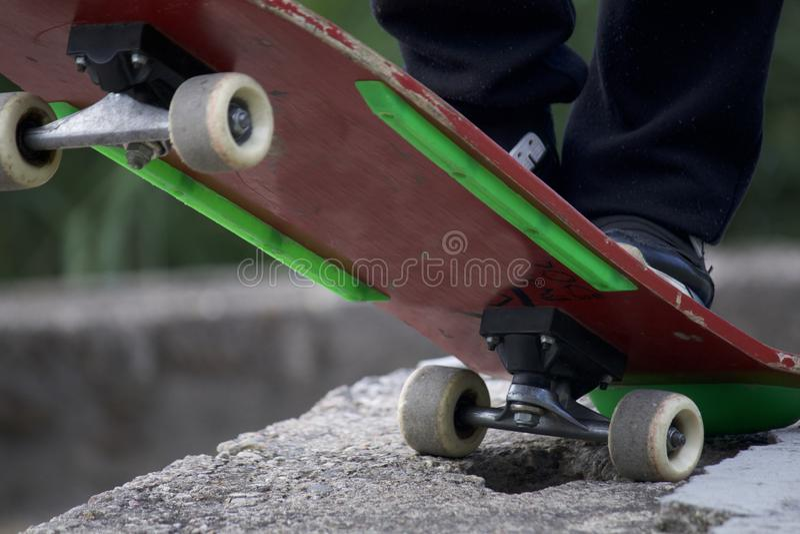 Um adolescente está estando em um skate imagem de stock