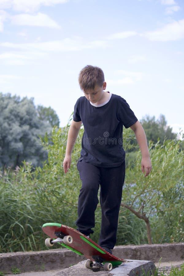 Um adolescente está estando em um skate imagens de stock royalty free