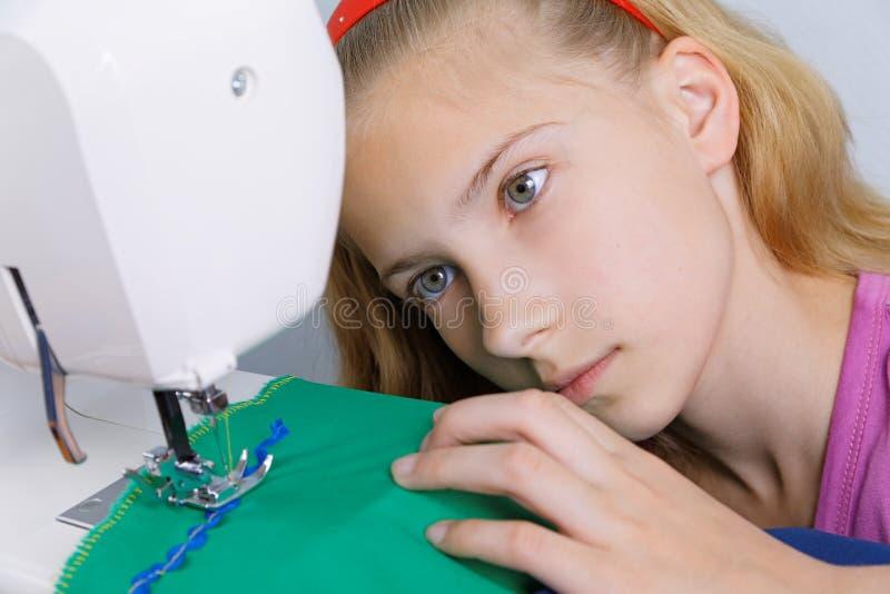Um adolescente está interessado em processo da costura na máquina de costura imagem de stock