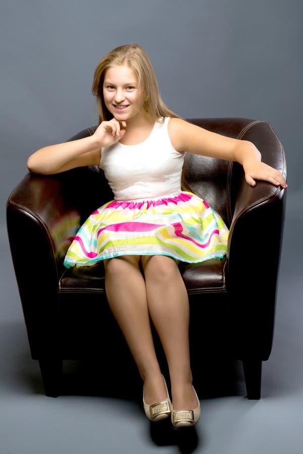 Um adolescente está sentando-se em uma cadeira de couro fotografia de stock